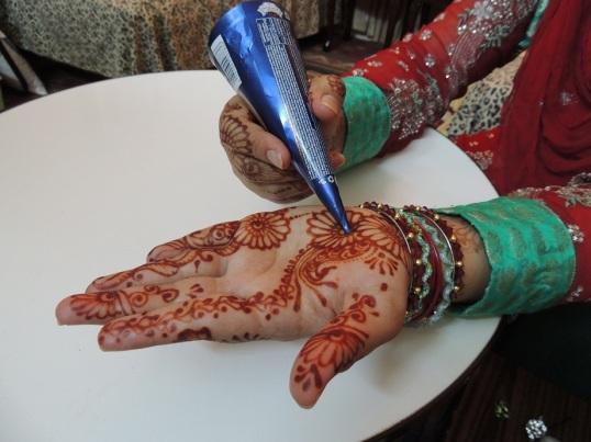 Ladies apply mehndi (henna) on Chand Raat.